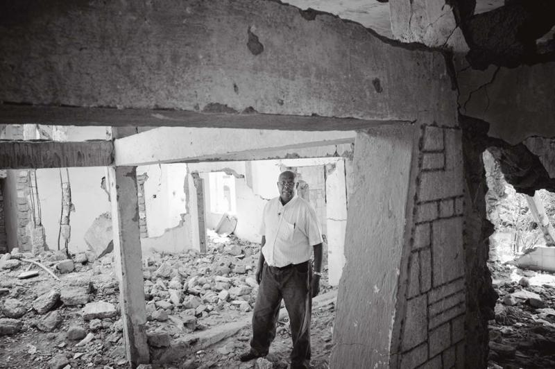 Dr. Aden Ismail stands in the ruins of his former mater- nity clinic. After the war, he qualified as a psychiatrist and returns now each year to treat those suffering from post-traumatic stress disorder.