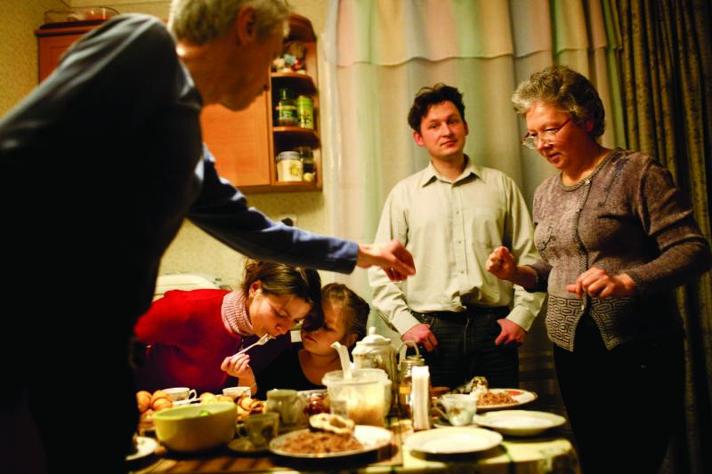 Dmitri Stelmakh and his family—including his wife, Aleksandra, stepdaughter Tanya, father Anatoliy and mother Tanya—sit down to eat a family meal at his parent's cottage in Slavutych. Dmitri grew up in Pripyat where his father was deputy chief of police when the accident occurred.