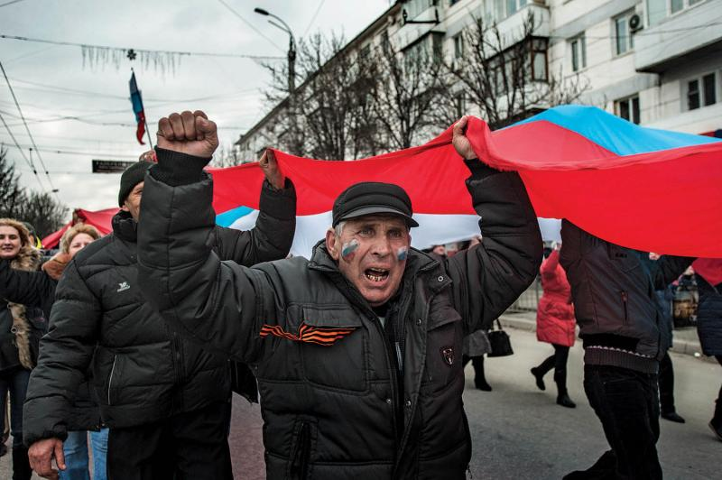 "Pro-Russian supporters at a rally in Simferopol, March 9, 2014. Russian president Vladimir Putin officially recognized Crimea's ""reunification"" with Russia on March 18, 2014."