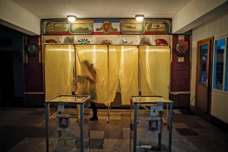 A voter at a polling station in Simferopol, March 16, 2014. On the wall behind the voting booth are various Soviet memorabilia, including the flag of the former Soviet Union and a portrait of Vladimir Lenin.
