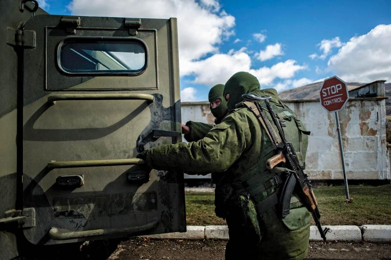Unidentified soldiers, believed to be Russian servicemen, preparing a blockade of a Ukrainian coast-guard base near the village of Perevalnoye. March 17, 2014.