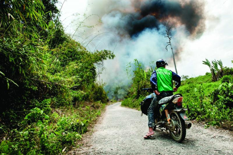 A motorcycle driver waits as a controlled fire burns on both sides of the one-lane road that connects the Naga Hills to the busy Chindwin River watershed. The slash-and-burn method is still the most common form of cultivation in the jungles of northeast Myanmar.