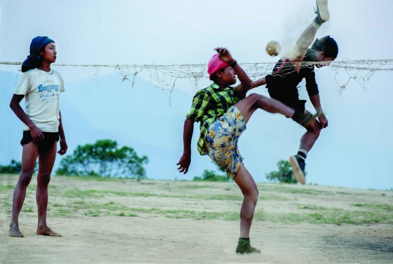 Boys play cane ball, a cross between soccer and volleyball, with a rattan ball on the plateau overlooking the valley below Layshee.