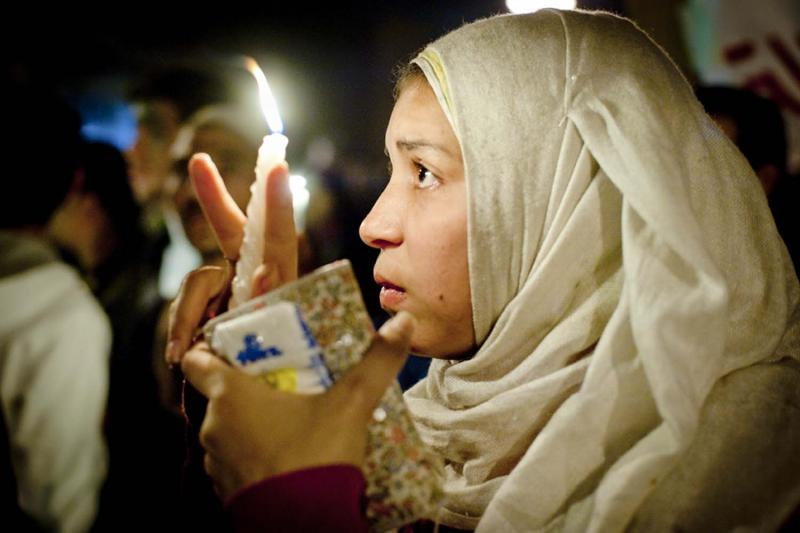 A young Egyptian woman carries a vigil candle in a ceremony honoring the shoheda, or martyrs—those Egyptians who died during protests in Tahrir Square. More than three hundred Egyptians perished in protests across the country.