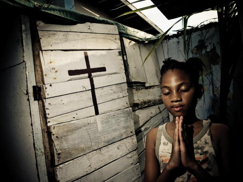 Annesha Taylor's daughter prays at an altar constructed in their backyard in Arnett Gardens in Kingston.