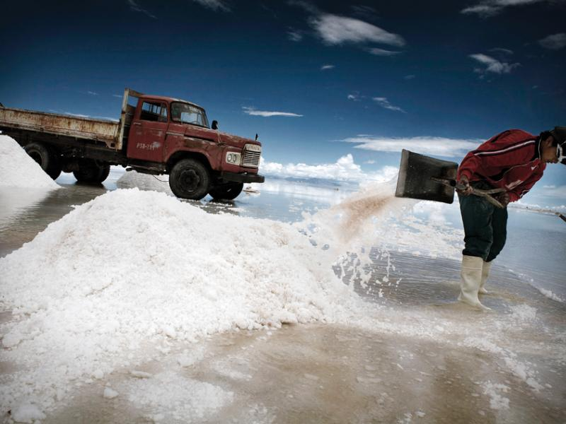 A miner piles salt to drain and cure on the edge of Bolivia's Salar de Uyuni, the world's largest salt flat. A fifty kilo bag sells for three bolivianos, about fifty cents.