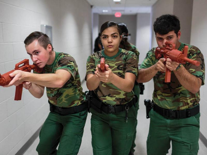 Ryan Dunlavy (left), Nerisa Garcia (center), and Jeremy Cabral (right), students from the Border Patrol Explorer Program, practice active-shooter scenarios and room clearing at the United States Border Patrol Station in Kingsville, TX. The Explorer program is a branch of the Boy Scouts of America and is sponsored by the US Department of Homeland Security. Photographed by Sarah Blesener